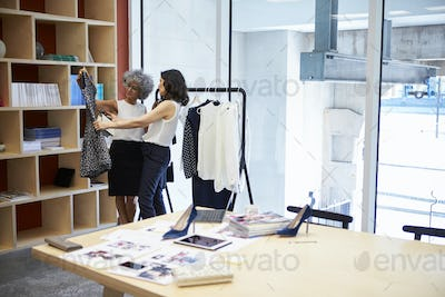 Two women discussing clothes in a creative media office