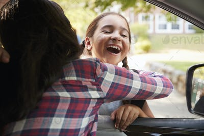 Mother In Car Collecting Daughter In Front Of School Gates