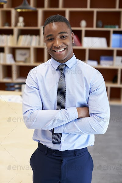 Young black man smiling to camera in a boardroom, vertical