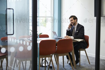 Young businessman making a phone call in a boardroom