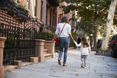Mother and daughter walking down the street, back view