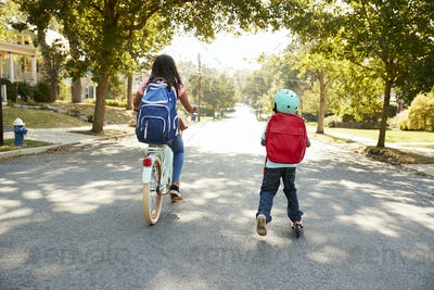 Sister With Brother Riding Scooter And Bike To School