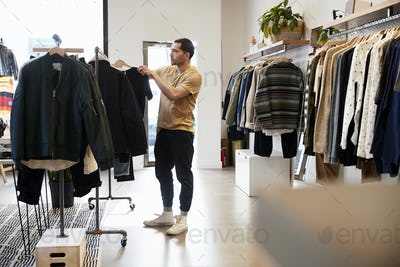 Young Hispanic man looking at clothes on a rail in a shop