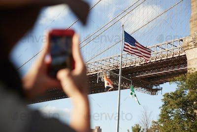 Tourist Taking Photo Of Brooklyn Bridge On Mobile Phone
