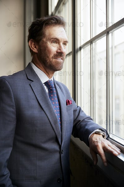 Senior white businessman looking out of window, vertical