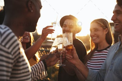 Friends making a toast at a rooftop party, close up