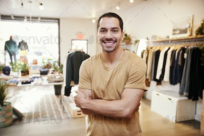 Young Hispanic man smiling to camera in a clothes shop