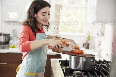 Woman cooking carrots in kitchen for Jewish passover meal