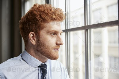 Young red haired bearded businessman looking out of window
