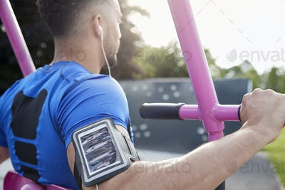 Young male athlete using outdoor gym, over shoulder view