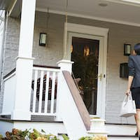 Businesswoman Returning To Suburban House After Work