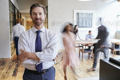 Portrait of middle aged white man in a busy modern workplace