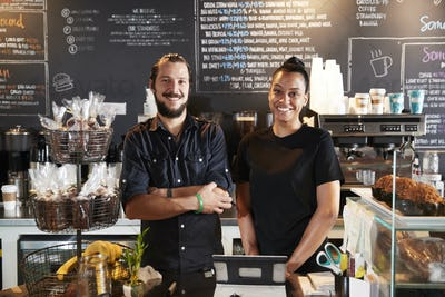 Male And Female Baristas Behind Counter In Coffee Shop