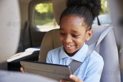 Boy Using Digital Tablet On Car Journey
