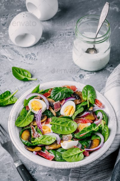 lunch bowl of spinach salad with bacon, mushrooms, eggs and red onions