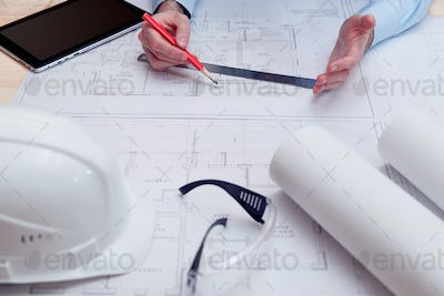 Chief engineer or architect works with building drawings
