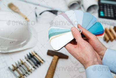 Architect interior's hands drawing home illustration with material sample, renovation concept.