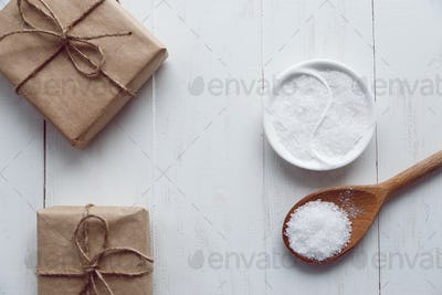 sea salt in bowl on wooden background, top view.
