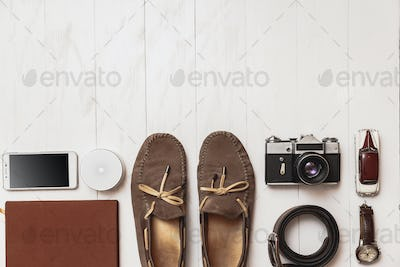 Set of men's blogger accessories for the traveler on a white wooden background.