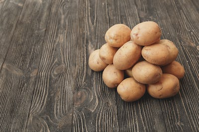 Handful of Raw harvested potatoes on dark wooden background
