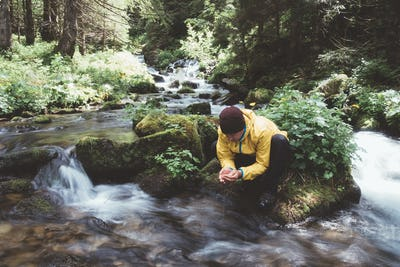 Man drink water from clear mountain stream