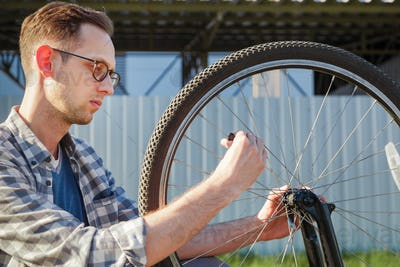 The mechanic man repair wheel of the bicycle. outdoor