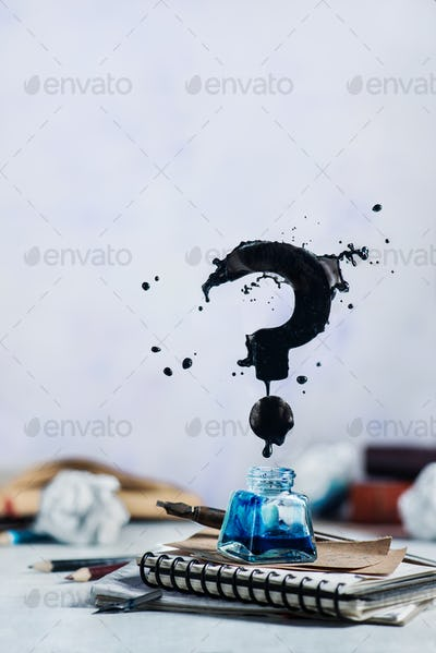 Spilled ink flying above inkwell in a splash in form of a question mark on a light background. Still