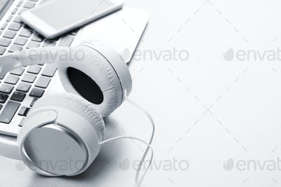 Headphones over laptop on wooden desk table