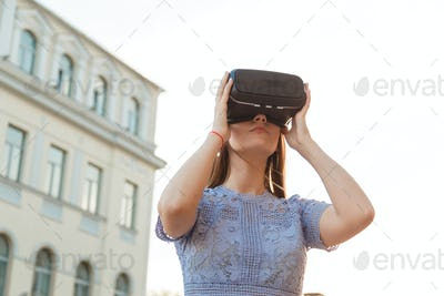 Young brunette is amused by her first encounter with futurist virtual reality glasses