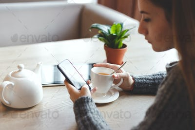 Young woman drink tea at restaurant and typing on smartphone