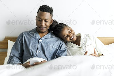 A happy couple using mobile phones in bed