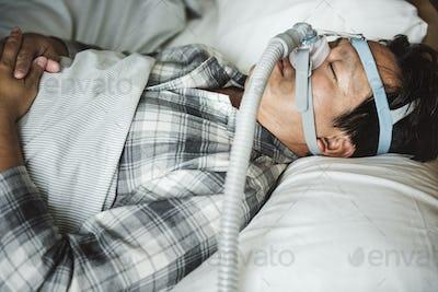 A man sleeping with anti snoring chin strap