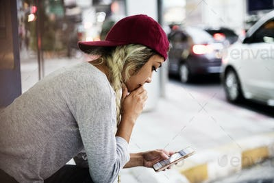 Serious woman using smartphone in the middle of the city