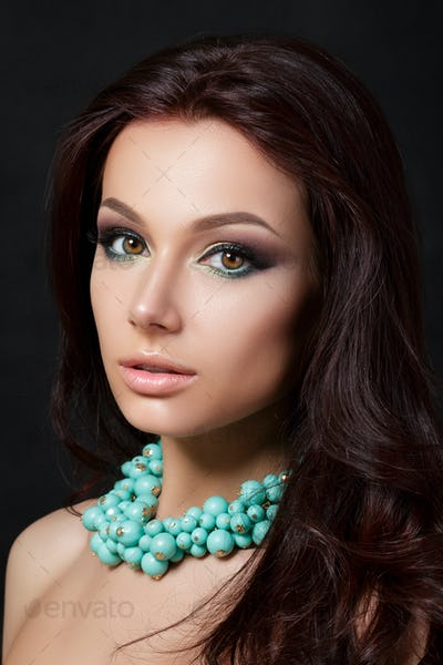 Portrait of young beautiful woman wearing blue necklace