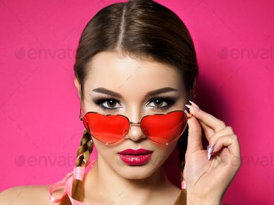 Young woman looks over heart shaped glasses