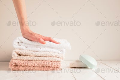 Woman's hand and a stack of soft towels