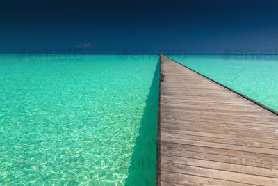 Wooden long jetty over lagoon with amazing clean azure water