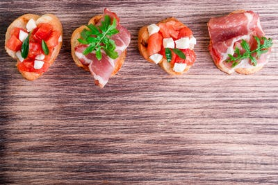 Set of bruschetta on wooden board.