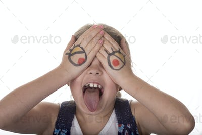 Little girl with eyes drawn on her hands making a goofy face