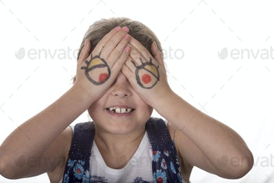 Little girl with cartoon eyes painted on her hands making goofy
