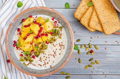 Tasty and healthy oatmeal porridge with mango, pomegranate and seeds