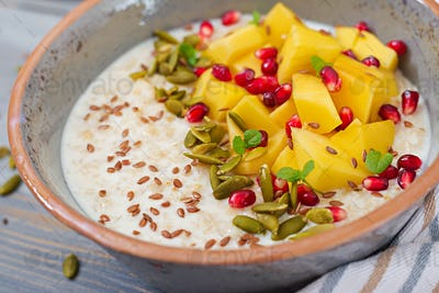 Tasty and healthy oatmeal porridge with mango, pomegranate and seeds.