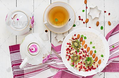 Tasty and healthy oatmeal porridge with kiwi, pomegranate and seeds