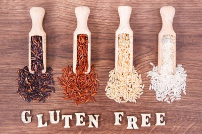 Black, red, brown and white rice on wooden scoop on rustic board, healthy food concept