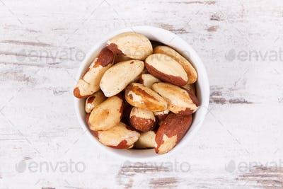 Brazil nuts in glass bowl on rustic board