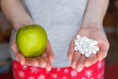 Woman holds a green apple in one hand and a handful of pills in the other.