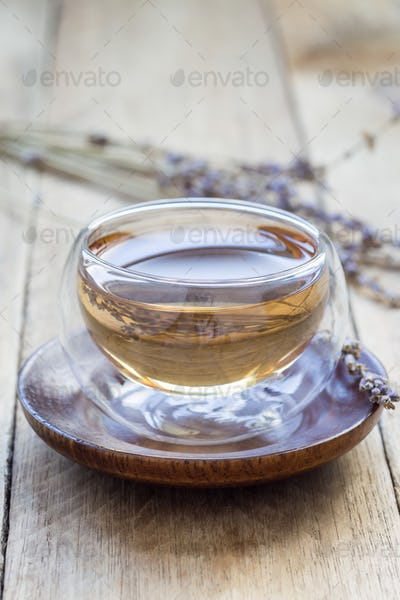 Healthy herbal lavender tea in oriental glass cup with lavender flowers on background, vertical