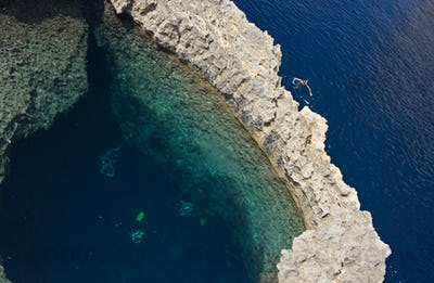 Snorkeler And Divers Near A Stone Arch, Malta