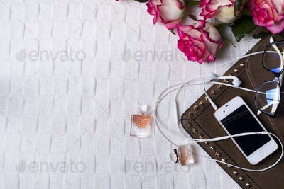 female clutch with phone, headphones and Perfume bottles with flowers