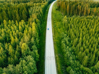 Aerial view from above of country road through the green summer forest in summer Finland.